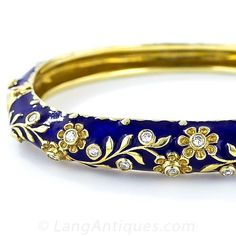 This solid and substantial hinged bangle bracelet, in 14 karat yellow gold, is gracefully adorned all around with a flowing foliate motif overlaying a rich deep cobalt blue enamel background. The flowers on the top half of the bangle sparkle with tiny bri Diamond Bangle, Diamond Jewelry, Gold Jewelry, Jewelery, Jewelry Accessories, Jewelry Design, Glass Jewelry, Gold Bangles, Bangle Bracelets