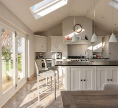Lloyd Loom barstools sit at the end of a custom kitchen with island unit, bathed in natural light by Velux windows. The kitchen designers at Cheshire Furniture Company have over 25 years of experience in crafting beautiful interiors.