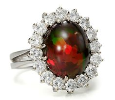 Chocolate Opal Diamond Cluster Estate Ring  | This opal was extracted from a mine in the Shewa Province, Ethiopia. Untreated and cut into an 5.5 carat oval cabochon, surrounded by (16) brilliant cut diamonds.