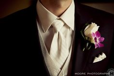 A white rose accented with a fuchsia dendrobium orchid. Photo by Moore Photography.