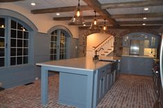 This striking kitchen brick floor is the Lancaster Running Bond brick tiles, It is the Providence color mix, with grout left in the texture.