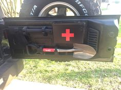 Jeep Wrangler tailgate shovel hatchet first aid storage.