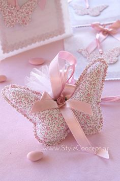 Χειροποίητη πεταλούδα μαξιλαράκι σε ροζ floral μοτίβο. Μια επιλογή που θα αποτελέσει μια πρωτότυπη μπομπονιέρα βάπτισης αλλά και ένα διακοσμητικό αναμνηστικό που θα κρατήσουν οι καλεσμένοι σας. Με τελείωμα ζιγκ ζαγκ, φιόγκο και θηλάκι από ροζ σατέν κορδέλα και ροζ σατέν ανθάκι η πεταλούδα μπομπονιέρα εντυπωσιάζει με τις προσεγμένες λεπτομέρειες. Η διάστασή της είναι 17χ 11εκ. Τα 4 κουφέτα κουφέτα αμυγδάλου Χατζηγιαννάκη περιέχονται σε λευκό τούλι που δένεται με λεπτές ροζ κορδέλες.