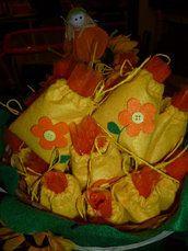SACCHETTI IN PANNOLENCI REALIZZATI A MANO con applicazione di fiore in pannolenci di colore arancio e bottoncino di colore giallo al centro, mentre lo stelo ( su ogni sacchetto lo stelo si trova in posizioni diverse) è ricamato a mano a punto erba ( dimensioni del sacchetto 12 × 9,5 alla base). Ciascun sacchetto è chiuso con cordoncino in carta di colore giallo e viene fornito di velo di colore arancio, cartene e bigliettino bianco.