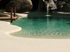 Piscina de arena realizada en Pontedeume (Galicia) en el jardín de una vivienda familiar. Tiene cascada, un pequeño río artificial y un muelle de madera IPE desde el que los niños de la familia disfrutan tirándose. Un oasis familiar. #piscinasdearena #piscinas #arena #complementos #familia