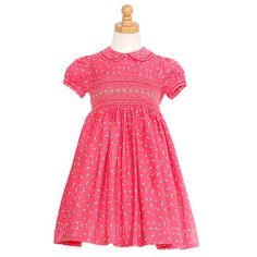 Coral colored smocked dress by Carriage Boutiques recaptures all the charm of little girls' clothes from days gone by. This beautiful dress is made of soft, fine wale corduroy printed with a pretty floral pattern. Exquisite details include smocking on fro