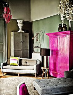 Colorful eclectic Mexico City living room with fuchsia painted wardrobe and chandelier.
