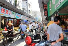 China, Hainan, Haikou - October 2, 2017: Asian street market on Haikou Qilou Old Street. Traffic in the urban market. All buyers ride mopeds. This street market is a famous landmark. Soft focus