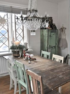 Love the chandelier, the mis matched chairs and the rustic table - all mixed together.