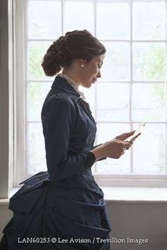 © Lee Avison / Trevillion Images - Victorian-woman-reading-letter-beside-window
