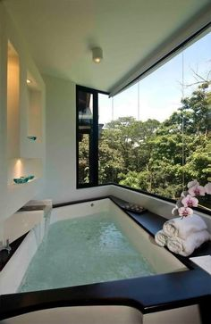 Beautiful tub with waterfall tub filler and relaxing view.