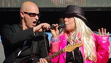 Missing Persons is an American band that plays a blend of new wave and hard rock. The band was founded in 1980 in Los Angeles by guitarist Warren Cuccurullo, vocalist Dale Bozzio, and drummer Terry Bozzio. They later added bassist Patrick O'Hearn and keyboardist Chuck Wild. Dale's quirky voice and heavy makeup made the band a favorite on MTV in the early 1980s. Her revealing outfits played a pivotal role in moving the culture of music videos towards that of overt sexual exhibitionism.