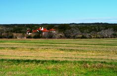 AGRICULTURAL / RECREATIONAL / EQUINE LAND WITH HOME FOR SALE in Dripping Springs, Hays County, Texas. 22 acres perfect for a vineyard, orchard, or hay production, with a custom 5,000 sq ft home right on the banks of Onion Creek, and a 5-stall horse barn.