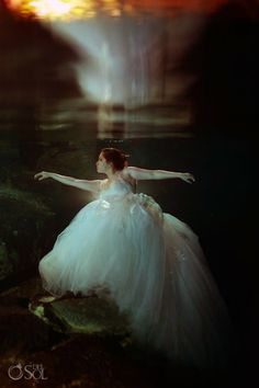 Mermaid bride in a @Pronovias gown underwater in a cenote in the Riviera Maya. Mexico wedding photographers Del Sol Photography.
