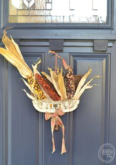Reuse an old dustpan to make a fall wreath. Just fill it with Indian corn and tie a ribbon through a hole in the top. An easy and unique fall decoration!