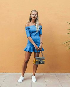 9 Looks casuais com vestido para você investir agora. Tênis branco, vestido azul com decote ombro a ombro e babados