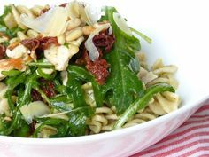 pastasalade met gerookte kip, rucola, zongedroogde tomaatjes, pesto en pijnboompitjes