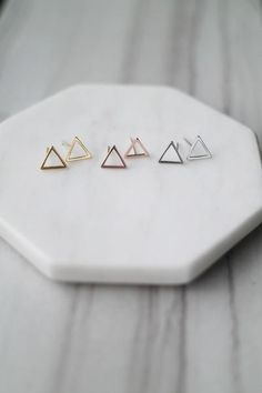 """These triangle outline earrings are perfect for everyday wear. Details: - .4"""" length - Post backs - Plated metal"""