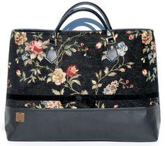 Fekete textilbőr és fekete rózsás textil kombinációjából készült táska. A táska 42cm széles és 29cm magas. Felül cipzáras, belül két részre osztott, és két zsebet is rejt, amik közül az egyik cipzáras. A vállpánt valódi bőr, hossza 40cm.