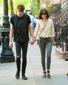 Dakota Johnson Might Be Wearing the Best Look for Spring: A linen button-down blouse provides an easy base for Johnson's look, while a knotted closure at the waist lends it a dose of devil-may-care attitude. Skinny gray Mother jeans are cropped just above the ankle to show off her sandals, while a braided leather belt adds contrast and a vintage feel. A petite cross-body bag and classic Wayfarer shades tie the look together—as does Johnson's rock-star boyfriend, Matthew Hitt.
