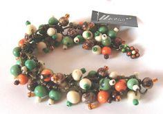Conjunto de pulseira e brincos confeccionados em níquel ouro envelhecido com contas de semente de açai e miçangas de vidro e tons de beje, verde e laranja; fecho lagssta. R$ 50,00