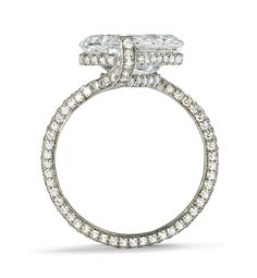 Twist Ring | Sotheby's Diamonds, The traditional diamond solitaire with a twist.  Centering an emerald-cut diamond weighing 4.06 carats, with additional pavé set diamonds. Mounted in platinum.