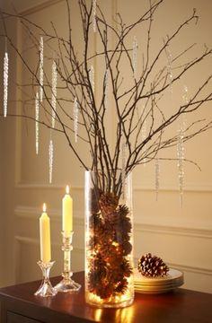 Jarrón con piñas acompañadas de velas
