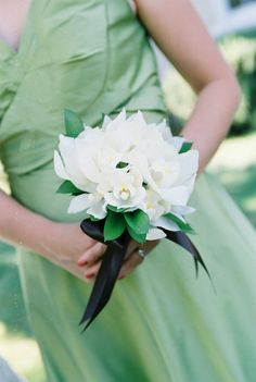 A clean and simple bridesmaid bouquet of white Cymbidium Orchids with a collar of Ruscus - by Heather Murdock of The Blue Orchid