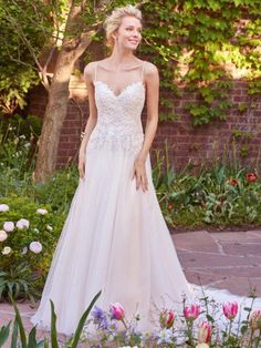 Rebecca Ingram - MARJORIE, Flirty strap details create a crisscross effect that accents the open plunging back in this tulle A-line wedding dress. Featuring a beaded lace bodice, V-neck, and flowing train. Finished with zipper closure.