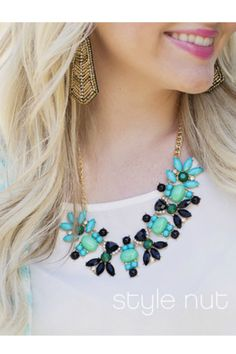 Gold tone floral bib necklace with mint green, turquoise, and black stones