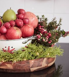 A bowl displays winter fruits, vegetables and greenery.