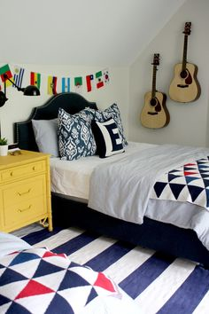boy's bedroom, yellow, gold navy, white, flags, striped rug, upholstered headboard