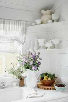 A cute corner shelf doesn't look cluttered when you group curvy pitchers and bowls in similar hues (and fresh cut flowers are always a happy accent).