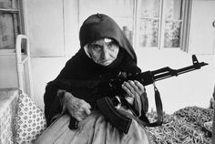 Senior citizens on the front line: 106-year old Armenian woman packs her assault rifle for fear of attack by Muslim, Turkish-speaking militiamen, 1990. Her expression says she will use the weapon if need arises.