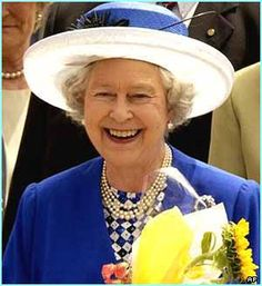 Her Majesty in a colbalt blue ensemble with white checks and a 4 strand pearl necklace and brooch to complete the outfit.