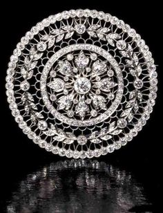 A Belle Epoque diamond brooch, by T.B. Starr & Co, circa 1915. The circular plaque set to the centre with an old brilliant-cut diamond flowerhead motif, within a garland surround and an outer border of further old brilliant-cut diamonds, against a ground of finely pierced tracery detail, signed T.B. Starr, French import marks. #Starr #BelleÉpoque #brooch