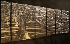 Whisper Metal Wall Art. Talented artist Ash Carl creates hand-sanded patterns on metal and after that he paints them and together they create the most incredible hologram effects as seen in this Whisper Metal Wall Art. When light is added you will see the artwork come to life. When you move around the room the design will change over and over again as it picks up new angles of light.