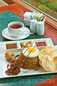 Indonesian fried rice with a sinful chicken satay, perfectly cooked sunny side egg and chicken wings. Simply delicious for breakfast or lunch! http://www.yukmakan.com