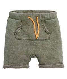 Khaki green. Shorts in lightweight sweatshirt fabric. Elasticized waistband with contrasting drawstring, kangaroo pocket at front, and sewn cuffs at hems.