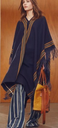 Shop now. Chloé Wool Poncho With Stripes. Clare Waight Keller just made us fall in love with ponchos all over again. This urban, sophisticated serape-style wool blanket poncho comes in elegant navy, is emblazoned with bold camel stripes and finished with raw edges. Luxuriously thick and cosy, it's like wearing your favourite blanket outside – except chic.