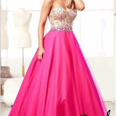 MacDuggal Nude & Fuchsia Ball Gown This classic ball gown with added embellishments will really make you sparkle. The strapless sweetheart neckline creates that princess affect that you have been dreaming of. Heatset stones are placed on the nude bodice with more beading along the waistline. A lace-up corset back makes this dress more comfortable and easy to make more form-fitting to your figure. Soft layers of tulle drape down over the flowing satin skirt and gracefully sweep across the…
