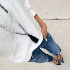 White relaxed sweater + black tassel necklace + distressed jeans + Rockstuds
