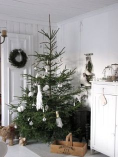 White Christmas decor with vintage touches, wreath and beautiful fresh Christmas tree