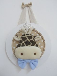 Quadro redondo em MDF, fundo forrado em tecido, resina e girafa em plush. O tecido do fundo do quadrinho e a alça, podem ser em outras cores. R$ 98,00