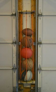 Need to organize your garage? This DIY sports ball holder uses space between the garage doors to organize your space.