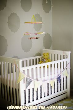 Love the graphic stenciled accent wall paired with the sweet DIY pinwheel mobile.
