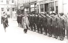 Op deze foto van Zutphen tijdens de oorlog in 1944 inspecteert burgemeester Tesebelt, lid van de NSB, de Nationaal Socialistische Beweging; de politie en enkele hoofden van de Luchtbeschermingsdienst op de Groenmarkt.