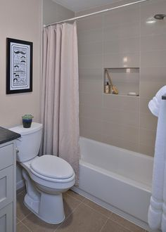 This updated guest bathroom features a shower with large subway tile, bath accessory niche, and brand new fixtures. Throughout the house, the Marron Cohiba granite was used as countertop material to help with cost, as well as keep some high contrast and interest with its organic, textured finish.