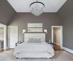 Honey-colored wood floors balance the cool color scheme of this room. The tufted white bench complements the bed linens while the acrylic legs bring a modern touch. The wall art brings small pops of color to the room while the slightly angled walls lead the eye up to the stunning chandelier.