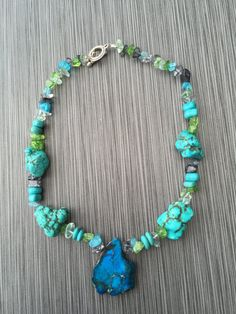 Materials:  - Dyed howlite chips, green/blue/black - 4mmX7mm dyed howlite beads, turquoise - Dyed howlite stone nugget beads, turquoise - Jasper stone, blue - Stretchy metal wire - Toggle clasp, silver  • Save 10% on your entire order when you spend $60 or more! Use coupon code SUMMER10 at checkout. Pictured here is a 20 inch necklace (10 inches each side). The blue stone hangs down an additional 1 1/2 in. from the bottom of the necklace.